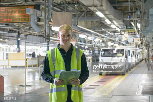 Portrait of apprentice engineer holding clipboard on car production line in car factory