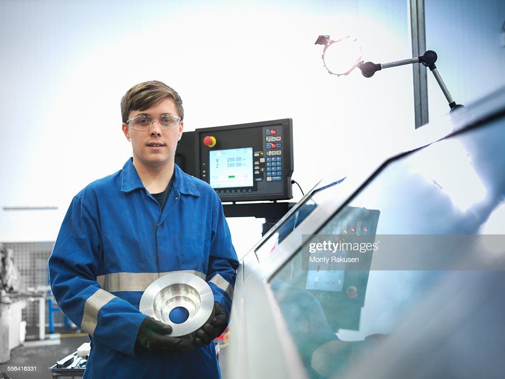 Portrait of apprentice engineer holding steel component with lathe in engineering factory