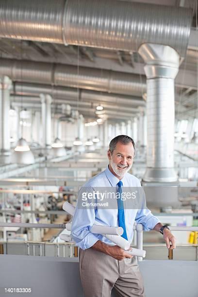 Porträt eines Architekten mit der Pläne liegen vor Fabrik