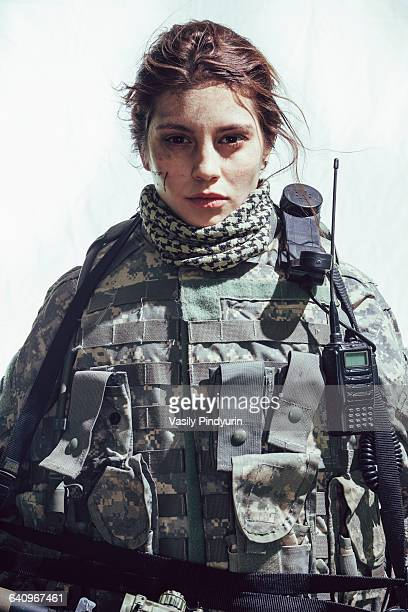 Portrait of army soldier standing against white background