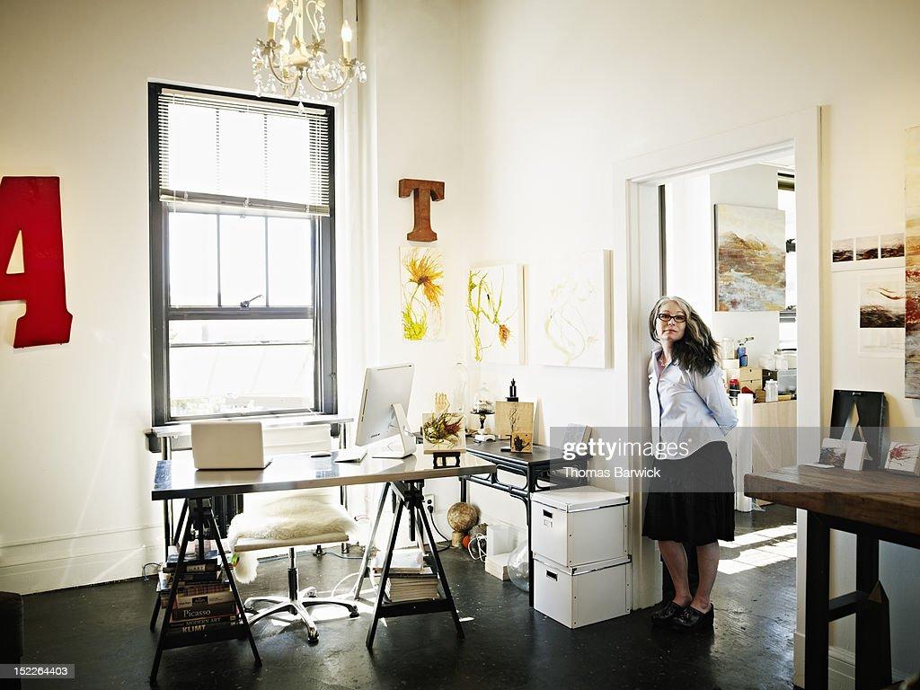 Portrait of artist standing in doorway of studio : Stock Photo