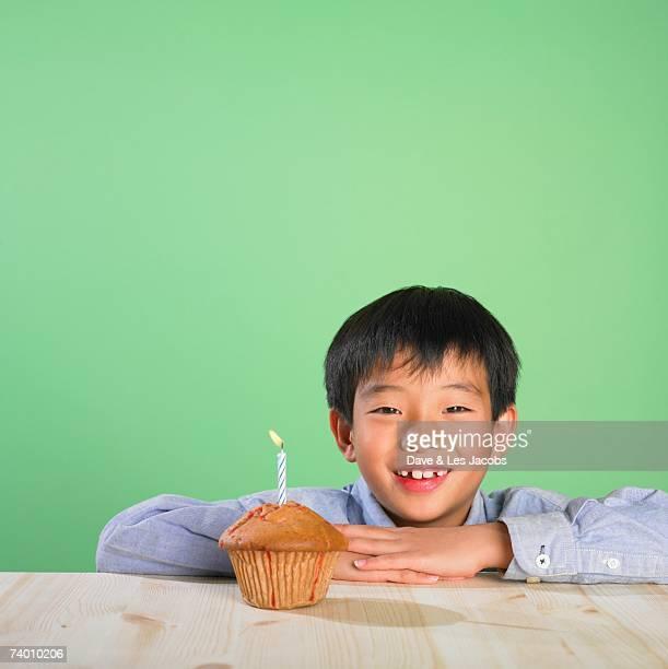 Portrait of Asian boy with birthday cupcake