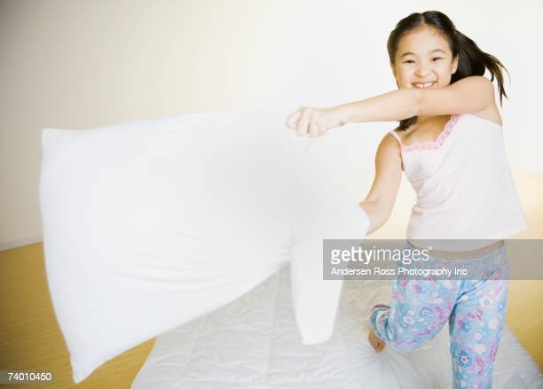 Portrait of Asian girl having pillow fight
