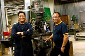 Portrait of Asian machinists in work shop.