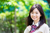 portrait of asian school girl in park