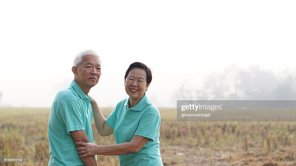 Portrait of Asian senior couple on bright green background : Foto de stock
