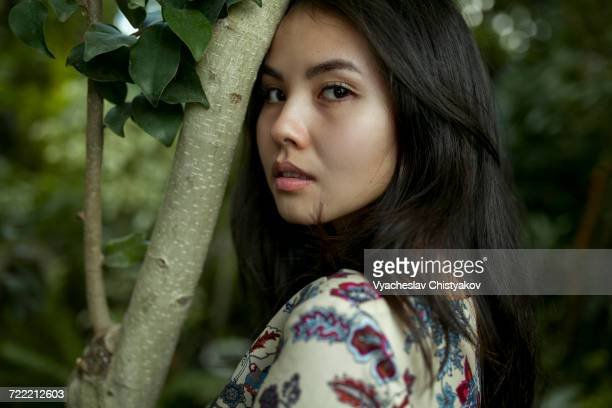 Portrait of Asian woman leaning forehead on tree branch