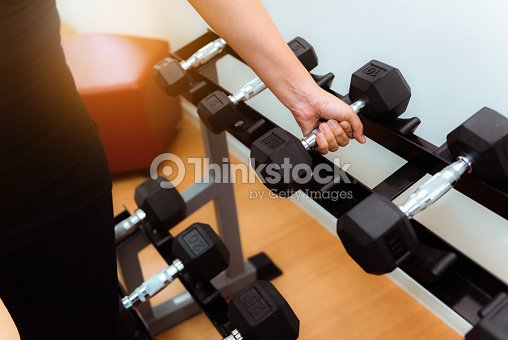 Portrait Of Asian Woman Lifting Dumbbells In Fitness Gym