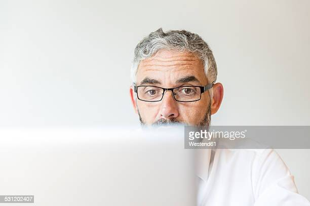 Portrait of astonished businessman working at laptop