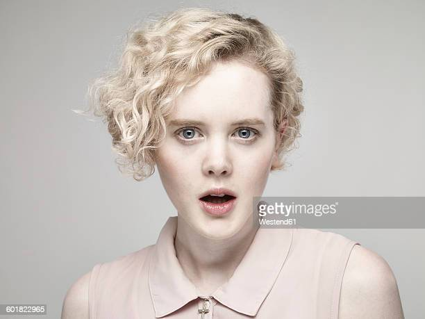 Portrait of astonished young woman in front of grey background