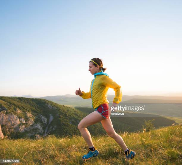 Portrait of athletic young woman trail running outdoor in nature
