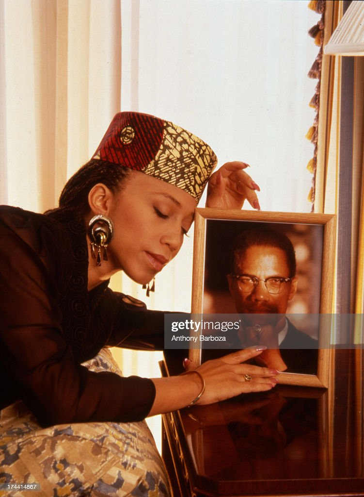 Portrait of <a gi-track='captionPersonalityLinkClicked' href=/galleries/search?phrase=Attallah+Shabazz&family=editorial&specificpeople=5363978 ng-click='$event.stopPropagation()'>Attallah Shabazz</a> as she poses with a framed portrait of her father, minister and Civil Rights activist Malcolm X, late twentieth century.
