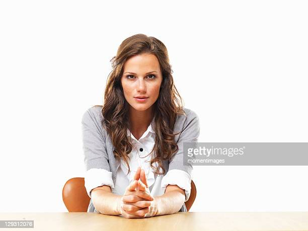 Portrait of attractive business woman sitting at table with hands clasped