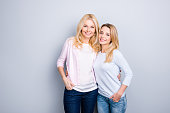 Portrait of attractive charming pretty cute similar mother and daughter embracing holding hands in pocket of pants standing over grey background