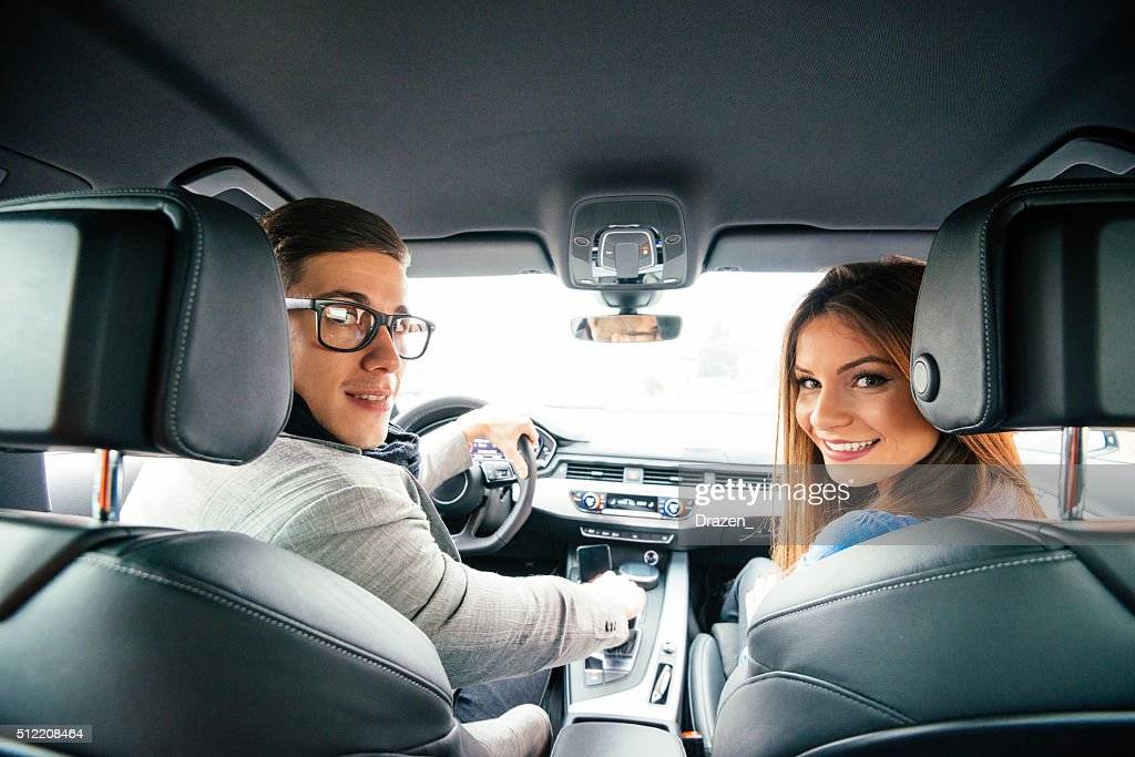 Portrait of attractive cheerful couple driving luxury car in city