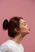 I kiss you. Portrait of attractive woman with kiss on lips. Pink studio. Beautiful female portrait. Young happy emotional funny woman looking at camera. Human facial emotions concept. Profile