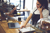 Female cashier with good mood making finance report at end in working day while talking with friends modern smartphone about meeting after job standing coffee