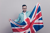 Portrait of attractive, handsome man in glasses and jeans shirt holding waving Jack Union flag
