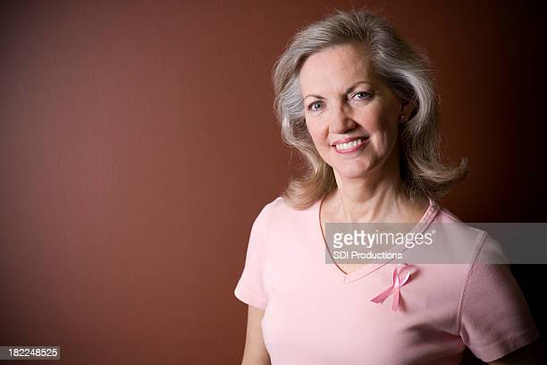 Portrait of Attractive Senior Adult with Breast Cancer Ribbon