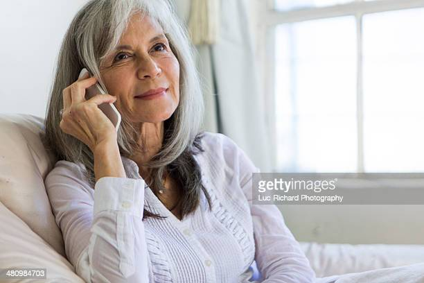 Portrait of attractive senior woman chatting on smartphone