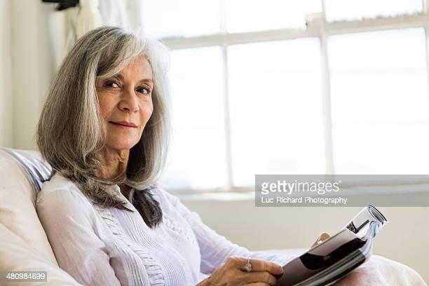 Portrait of attractive senior woman reading magazine