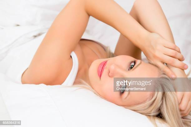 Portrait of attractive woman lying down on bed with hand in hair