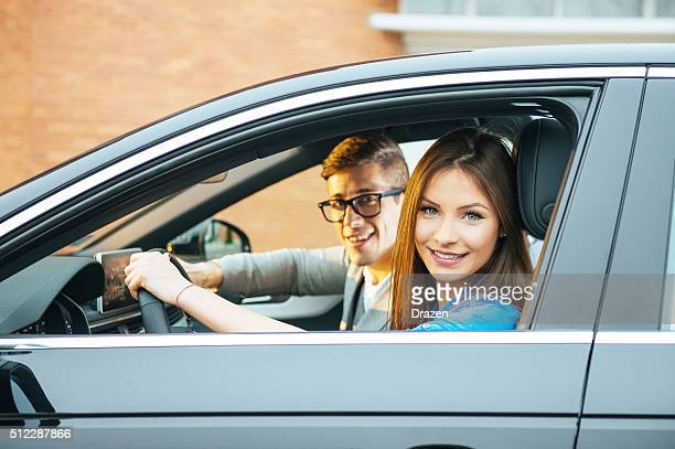 Portrait of attractive young couple driving black car in city