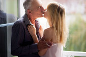 Portrait of Attractive Young Woman Kissing Her Senior Husband near Opened Windows in the Room During Summer Time. Age Difference Concept