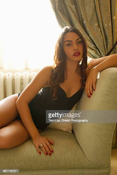 Portrait of attractive young woman reclining on chaise longue
