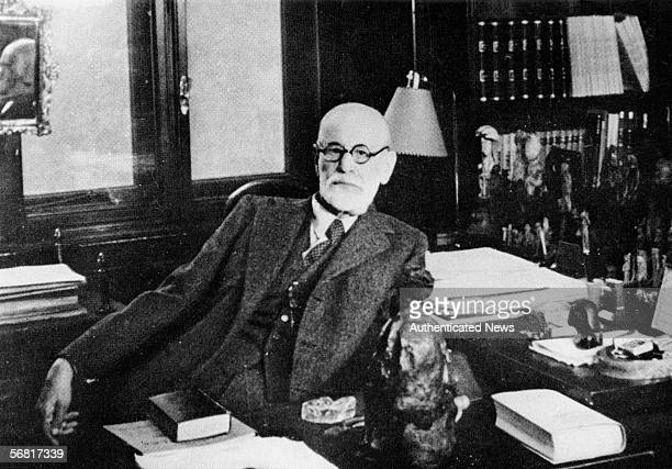 Portrait of Austrian psychologist Sigmund Freud as he sits behind his desk in his study Vienna Austria 1930s The office is filled with figurines and...