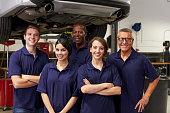 Portrait Of Auto Mechanics Working In Garage