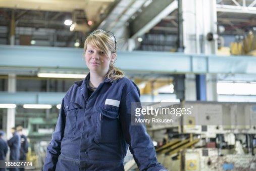 Portrait of automotive apprentice wearing boiler suit in car plant