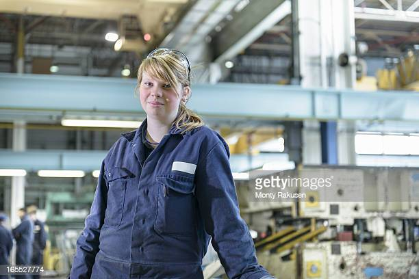 Portrait of automotive apprentice wearing boiler suit in car plant