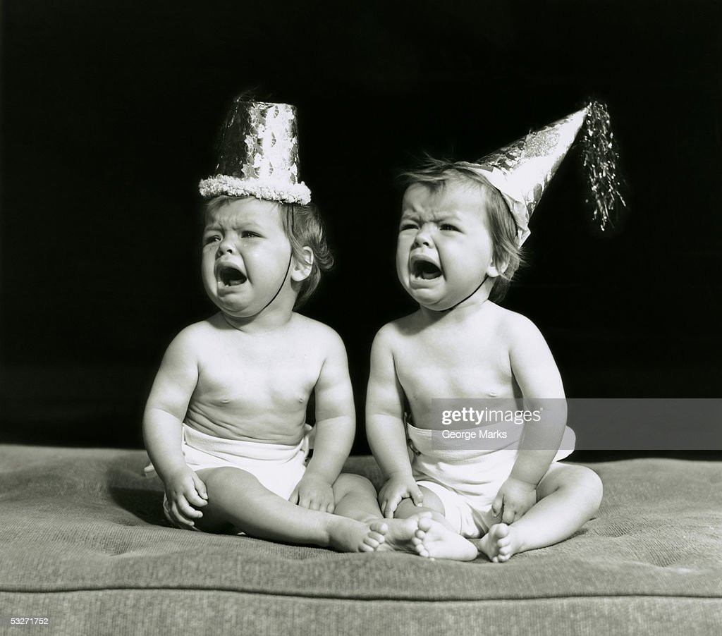 Portrait of babies wearing hats crying : Stock Photo