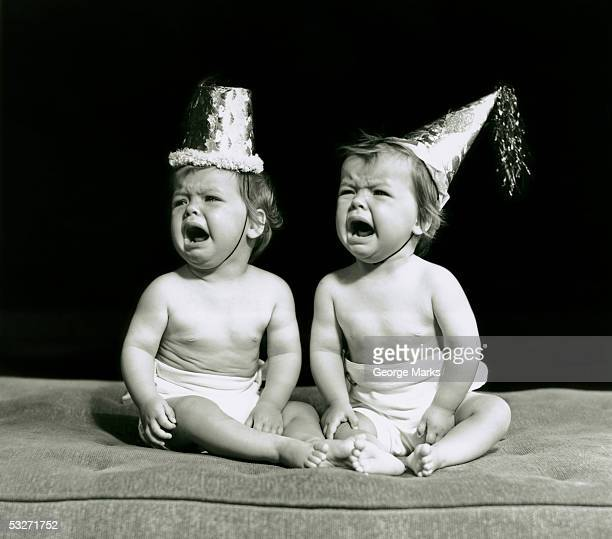 Portrait of babies wearing hats crying