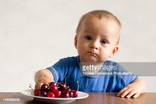Portrait of baby boy eating cherries : Stock Photo