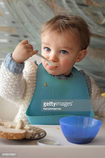 Portrait of baby boy (18-23 months) wearing baby bib eating at table