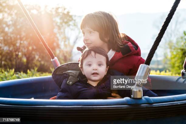 Portrait of baby boy with brother on playground ride in park