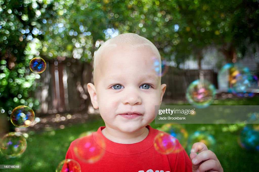 Portrait of baby boy with bubbles looking at camera : Stock Photo