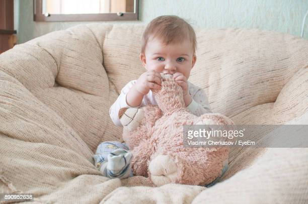 Portrait Of Baby Girl Biting Teddy Bear On Sofa At Home