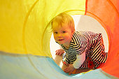 Portrait of baby girl crawling in multi-colour tunnel