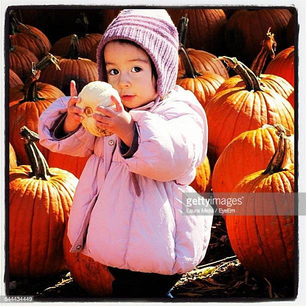 Portrait Of Baby Girl Holding Small Pumpkin Among Large In Botanical Garden