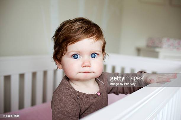 Portrait of baby girl in crib