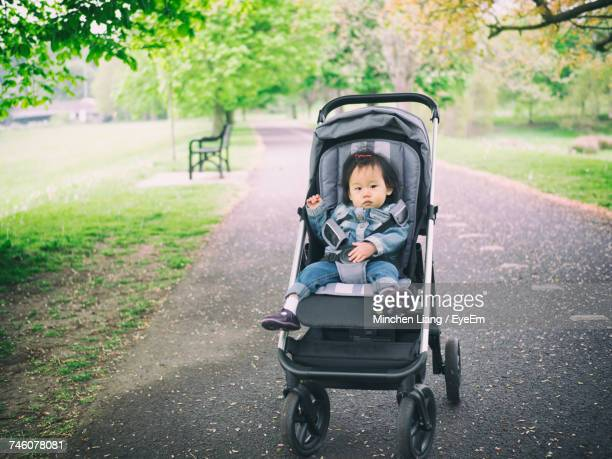 Portrait Of Baby Girl In Stroller On Road At Park