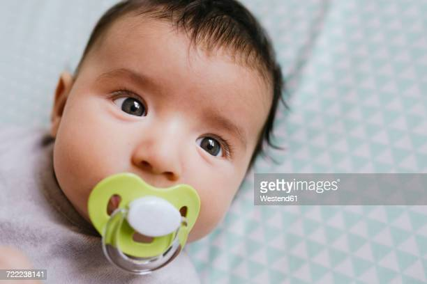 Portrait of baby girl lying on bed sucking a pacifier