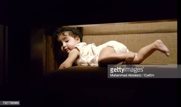 Portrait Of Baby Girl Lying On Chair Seen From Table