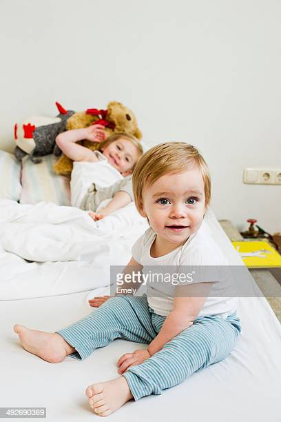 Portrait of baby girl on bed with her sister