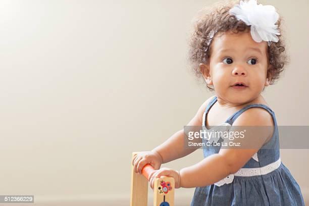 Portrait of baby girl, pushing baby walker