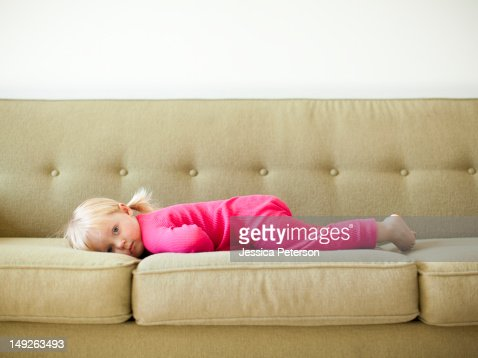 Portrait of baby girl (18-23 months) resting on sofa : Stock Photo