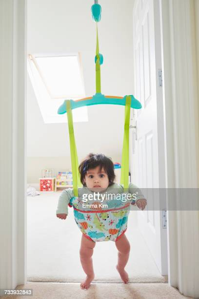 Portrait of baby girl staring from baby bouncer